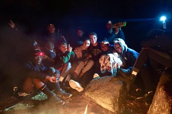 students gather around a late night campfire